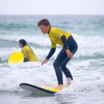 13 year old son up and riding the waves at Sennen Beach, courtesy of Smart Surf School