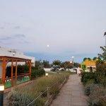 Vue du bar, qui donne sur les jeux et l'accès à la plage (qui commence au niveau des arbres au f