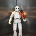 Robot playing the violin and poster of factory tour