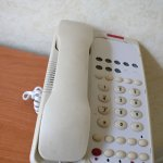 Dirty and stained phone in room, the information booklet was also dirty and sticky