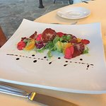Starter of beef carpaccio with some colourful petals and something that pops in your mouth!