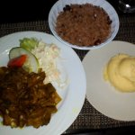 curried mutton with rice and peas and a side of mashed potatoes