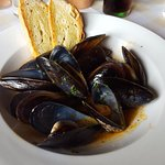 Starter of mussels in garlic and tomato broth with grilled bruschetta