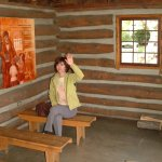 Lovely lady pretends to be student in replica of pioneer classroom.