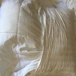 Lieblos gemachte Betten mit Kissen, die in viel zu kleine Kissenhüllen gestopft wurden
