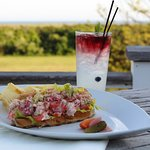 Enjoy a Lobster Roll on our outdoor deck at The Dunes, featuring lobster meat, celery & red onio