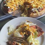 Taco Pizza on regular crust. Taco meat, onion, black olives, tomato, cheddar cheese, lettuce and