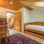 Ein Schlafraum der Suite mit Schreibtisch und Blick in den Wohnbereich.