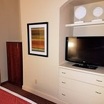 TV area. In corner is cabinet with microwave, coffeemaker, and fridge.