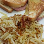 Grilled ham and cheese with a side of hash browns, looks greasy.
