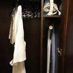 Small closet with robe, iron, and ironing board