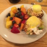 Eggs benedict with crab and a side of fruit salad