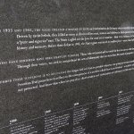 A stone marker at the memorial's entrance, containing some information about the Holocaust.
