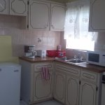 Kitchen with full amenities. microwave, stove, refrigerator, cooking utensils, plates, cups, for
