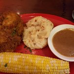 Chicken, mashed potatoes with gravy, and corn on the cob