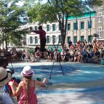 Clown juggling and balancing on a tight-rope delights children & adults in Place de l'Hotel de V