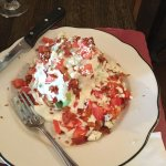 Iceberg lettuce wedge with bleu cheese dressing & bacon bits & tomato pieces