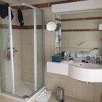 Vue de la douche et du lavabo dans la salle de bain
