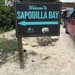 Sapodilla Bay. Cars park on the road side. Sapodilla Bay is across the street from Las Brisas Re