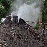 Un des charbonniers amateurs régule la carbonisation