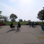 Some guests eat breakfast at tables outside overlooking Lake Michigan.