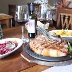 Fiorentina con contorno di cipolle rosse in agrodolce e patate al forno, accompagnato da Chianti