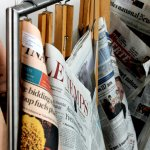 The daily papers on traditional wooden holders, near the café