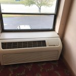 hallway non-functioning air conditioner-hole in screen dirt in the corner