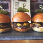 Wagyu Beef Sliders with American Cheese, Black Beer Onions, Horseradish Mayo & Baby Pickle.