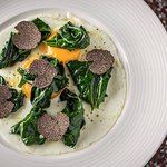 fried eggs with fresh spinach and aromatic black truffle