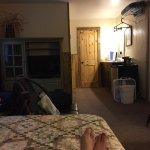 View from the bed. Refrigerator, fan, coffee pot (and coffee), toiletries, white fluffy towels.
