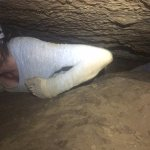 Belly crawling through the cave