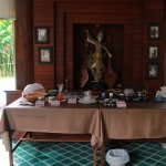 breakfast table with tea, coffee, confiture, fruits and yoghurt and cereals: