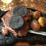 Sizzling steak on a hot skillet, black pudding and mushrooms.
