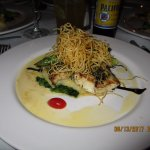 Crusted Sea Bass on a bed of garlic mashed potatoes with fried fine onions.