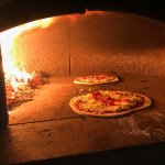 Pizzas being cooked in our outdoor wood burning oven