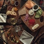 Left: veggie flatbread; back: charcuterie board with 2 meats and 2 cheeses; front: salmon board