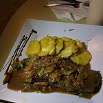 Steak topped with mushroom sauce and side of friend plantains