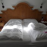Letto matrimoniale in stile Tirolese con piumoni e testata in legno.