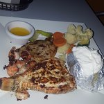 Grilled seafood combo with fish, lobster tail, shrimp, and veggies.