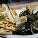 Steamed Littleneck Clams in a Bacon Sherry Broth, served with Grilled Sourdough