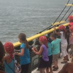 Kids are using water cannons to defend the ship against an attacking pirate.