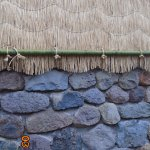 Straw mats protect clay walls above stone