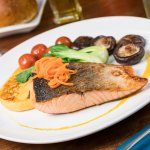 Salmon filet with orange chipotle sauce, mushrooms and manchego polenta