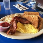 Scrambles eggs, bacon and dry hash browns with toast