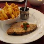 Longe de porc sauce corsée avec des frites maison.