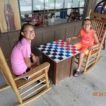 Our daughters Abby and Madison playing checkers in front of Cracker Barrel