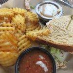 Half of a turkey club sandwich with waffle fries