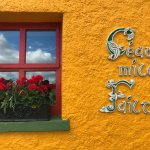 Beautifully welcoming mustard coloured Pancake House with Red windows and flowers.