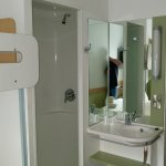 Small shower cubicle with hand basin in the room